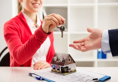 Smiling woman realtor giving key of new apartment to client